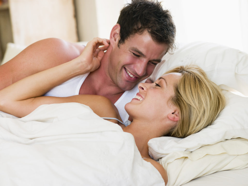 man and women awake in bed smiling